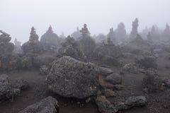 Piramids de piedra en la niebla, Kilimanjaro imagenes de archivo