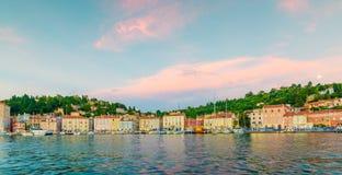 Piran hamn under solnedgången Mjukt och varmt ljus ovanför fartyg och Piran hus arkivfoton