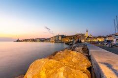 Piran Slovenië: Stadskust na de zonsondergang met nachtlichten in restaurants Kijk van de Piran-haven aan de Toerist van de stads royalty-vrije stock foto