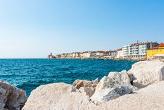 Piran, Slovenia: View of the Piran coast near the harbor. The medieval ancient city with church surrounded by Mediterranean sea. Hotels and tourist on the stock photos