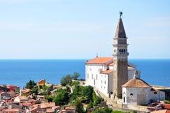 Piran stadstorn och kyrka i sunndag Arkivfoto