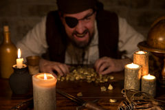 Pirat mit einem Schatz des Goldes hinter vielen Kerzen stockfotos