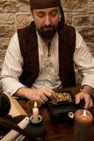 Pirata con la presa grande, la tabla con el tesoro del oro, las velas y v Fotos de archivo