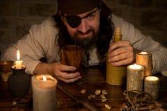 Pirata con ron y porciones de velas y de goldnuggets, concepto m fotografía de archivo libre de regalías