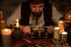 Pirata con un tesoro del oro, de muchas velas y del accesso viejo Imagen de archivo libre de regalías