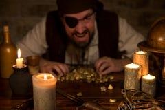 Pirata con un tesoro del oro detrás de muchas velas Fotos de archivo