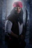Pirata hermoso que sostiene una espada fotografía de archivo