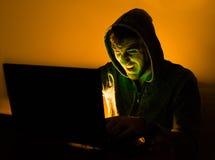 Pirata informático agresivo que grita al ordenador Imagenes de archivo