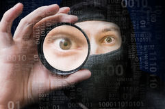 Pirata informático anónimo enmascarado que explora código binario imagen de archivo