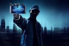 Pirata informático anónimo que sostiene el teléfono móvil foto de archivo libre de regalías