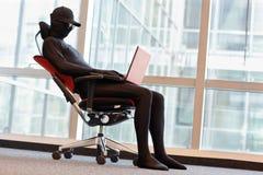 Pirata informático anónimo que trabaja con el ordenador portátil en oficina foto de archivo libre de regalías
