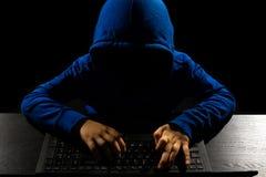 Pirata informático anónimo que usa el ordenador imágenes de archivo libres de regalías
