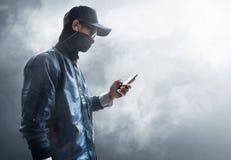 Pirata informático anónimo que usa el teléfono móvil imagenes de archivo