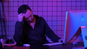 Pirata informático cansado que duerme cerca del ordenador mientras que tratamiento por ordenador imagenes de archivo