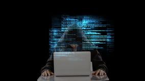 Pirata informático con el ordenador portátil y el vídeo de los códigos almacen de video