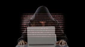 Pirata informático con el ordenador portátil y el vídeo de los códigos metrajes