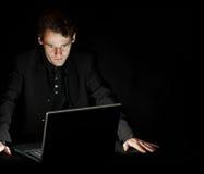 Pirata informático con la computadora portátil en sitio oscuro Imagen de archivo libre de regalías