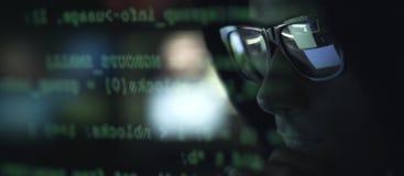 Pirata informático con las gafas de sol y código en la pantalla imagen de archivo