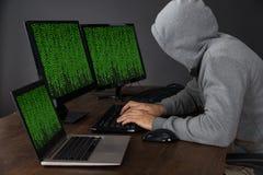 Pirata informático con los ordenadores en el escritorio imagen de archivo libre de regalías