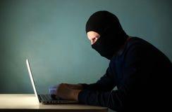 Pirata informático con un ordenador portátil en la máscara Fotografía de archivo libre de regalías
