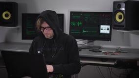 Pirata informático contento en una sudadera con capucha negra con el kayushonom del color que se sienta en su natbukom y dedicado metrajes