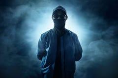 Pirata informático de ordenador anónimo en fondo del humo foto de archivo