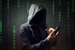 Pirata informático de ordenador con el teléfono móvil foto de archivo