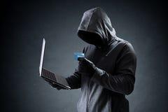 Pirata informático de ordenador con la tarjeta de crédito que roba datos de un ordenador portátil