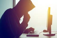 Pirata informático de ordenador encapuchado que corta la red fotografía de archivo