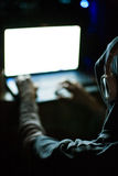 Pirata informático de ordenador que trabaja en el ordenador portátil en la oscuridad Imagen de archivo libre de regalías