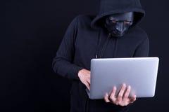 Pirata informático de sexo masculino con el ordenador portátil que lleva de la máscara negra foto de archivo libre de regalías