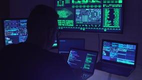 Pirata informático de sexo masculino que trabaja en un ordenador en un cuarto oscuro de la oficina metrajes