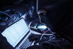 Pirata informático dentro del coche Foto de archivo libre de regalías