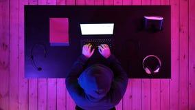 Pirata informático en código que mecanografía de la sudadera con capucha en programa usando el ordenador portátil en estudio oscu almacen de video