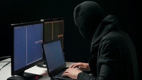 Pirata informático en código que se agrieta del pasamontañas usando el ordenador portátil y los ordenadores de su sitio oscuro de metrajes