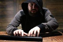 Pirata informático en la capilla negra en un cuarto con las paredes de madera fotos de archivo libres de regalías