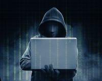 Pirata informático en ordenador portátil negro de la tenencia de la sudadera con capucha con su mano y código binario imagen de archivo