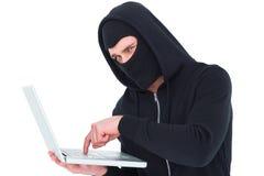 Pirata informático en pasamontañas que mecanografía en el ordenador portátil Imagen de archivo libre de regalías