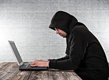 Pirata informático en sudadera con capucha negra con el ordenador portátil foto de archivo