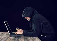 Pirata informático en sudadera con capucha negra con la tarjeta del ordenador portátil y de banco fotografía de archivo
