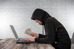 Pirata informático en sudadera con capucha negra con las notas del ordenador portátil y del dólar foto de archivo libre de regalías
