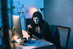 pirata informático encapuchado en la máscara que cuenta el dinero robado imágenes de archivo libres de regalías
