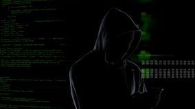 Pirata informático encapuchado irreconocible anónimo que usa smartphone para robar los datos, ciberdelincuencia almacen de video