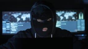 Pirata informático peligroso en los intentos de la máscara para incorporar el sistema usando códigos y números para descubrir la  metrajes