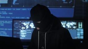 Pirata informático peligroso en los intentos de la máscara para incorporar el sistema usando códigos y números para descubrir la  almacen de metraje de vídeo
