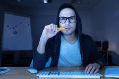 Pirata informático pensativo hermoso que se rompe en un sitio web fotografía de archivo libre de regalías