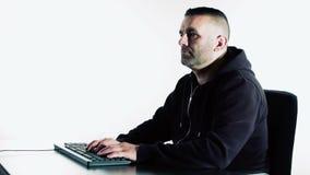 Pirata informático que mecanografía en el teclado negro, fondo blanco almacen de video