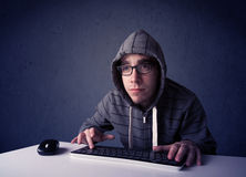 Pirata informático que trabaja con el teclado en fondo azul Foto de archivo