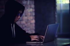 Pirata informático que trabaja en su ordenador, pirata informático que roba contraseña y el dat foto de archivo libre de regalías