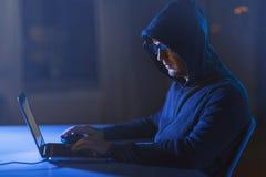 Pirata informático que usa el ordenador portátil para el ataque cibernético fotos de archivo
